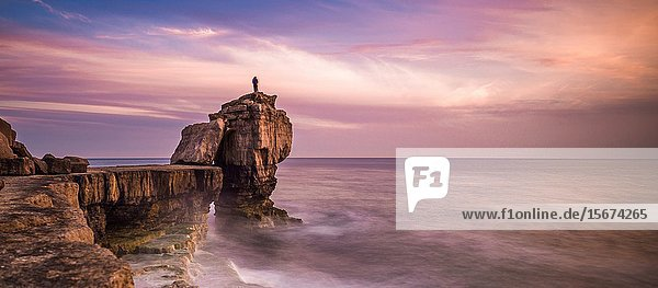 Man standing on top of Pulpit Rock at sunset  Portland Bill on the Isle of Portland near Weymouth on Dorset's Jurassic Coast. England. UK.