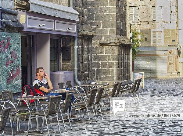 Man sitting in outdoor cafe on phone  Place de la Halle aux Bleds  Saint-Flour  Cantal Department  Auvergne  France.