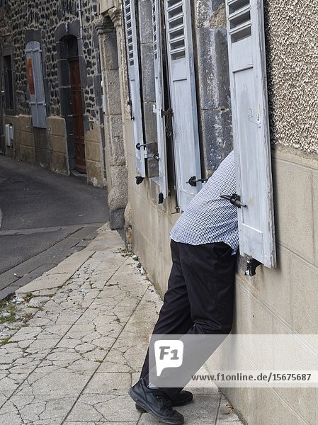 Man leaning in a window  Saint-Flour  Cantal Department  Auvergne  France.