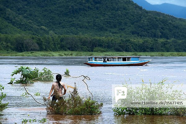 Young people fishing in the Mekong River  Chiang Rai to Luang Prabang  crossing Thailand to Laos in boat.