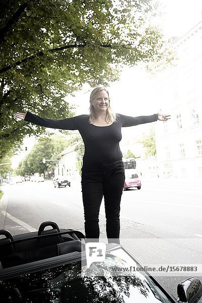 Woman standing on convertible car with arms open  Munich  Germany.