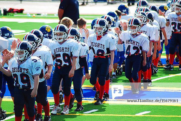 Two pee wee football teams shake hands at the end of the game.
