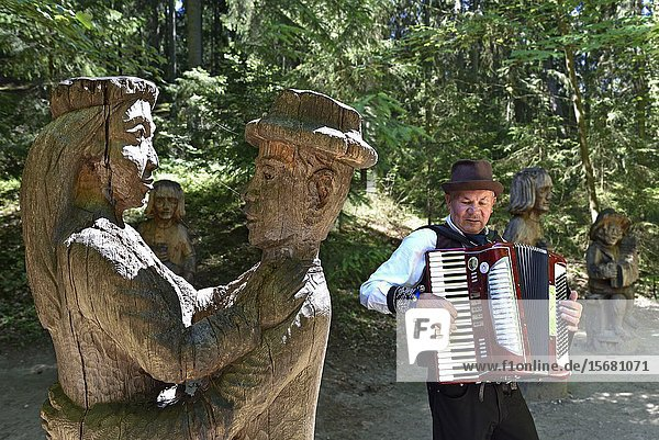 Musician amidst wooden statues along the outdoor wooden sculpture gallery on the Hill of Witches  near Juodkrante  Curonian Spit  Lithuania  Baltic States  North Europe.