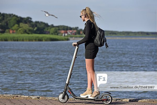Young woman riding scooter on the seaside promenade at Nida  Curonian Spit  Lithuania  Baltic States  North Europe.