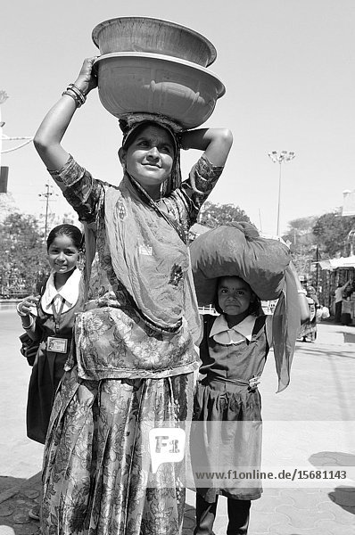 Patan: Indian woman with her two daughters carring water bowls on her head.
