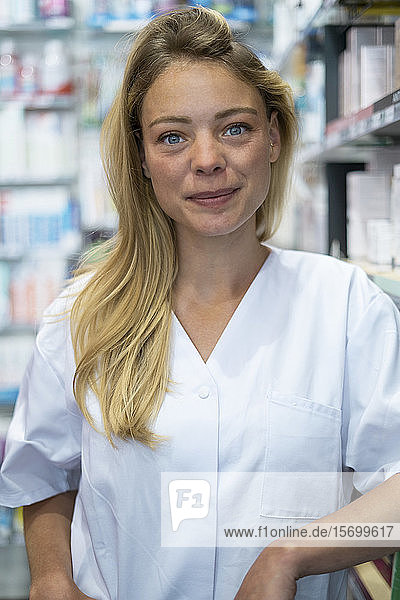 Portrait of smiling young woman standing in pharmacy