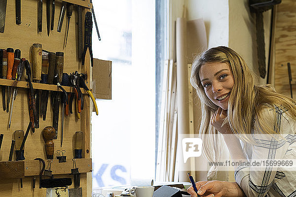 Woman writing on notepad in workshop