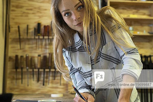 Woman holding pen in workshop