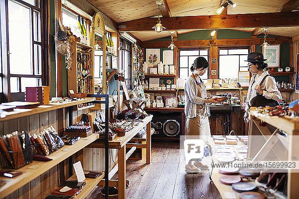 Japanerin mit Schürze steht in einem Ledergeschäft  hält eine Clutchbag aus hellbraunem Leder in der Hand und spricht mit einem Kunden.