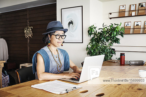 Female Japanese professional sitting at a table in a co-working space  using laptop computer.