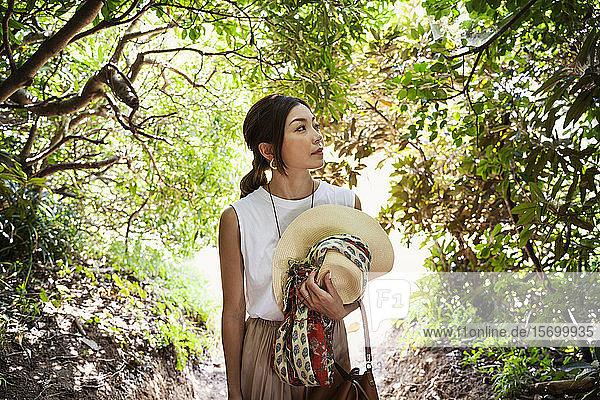 Japanische Frau mit Hut  die in einem Wald wandert.