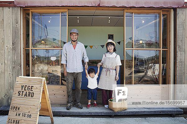 Japanischer Mann  Frau und Junge stehen vor einem Bauernladen  halten sich an den Händen und schauen in die Kamera.