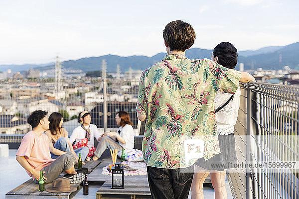 Gruppe junger japanischer Männer und Frauen auf einem Dach in einer städtischen Umgebung.