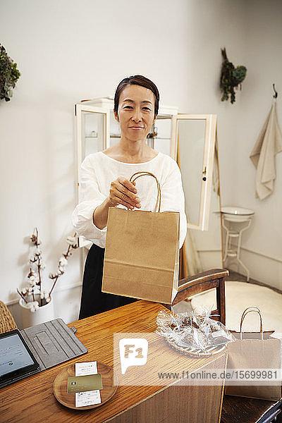 Lächelnde Japanerin steht in einer kleinen Modeboutique  hält eine braune Einkaufstasche aus Papier in der Hand und schaut in die Kamera.