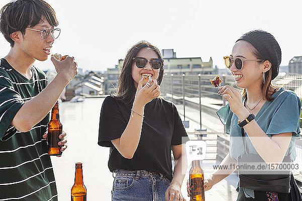 Ein junger Japaner und zwei Frauen stehen auf einem Dach in einer städtischen Umgebung und trinken Bier.