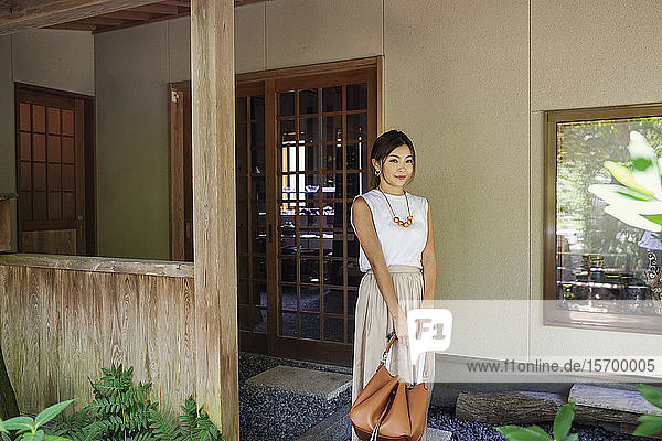 Japanese woman standing on a porch  holding handbag.