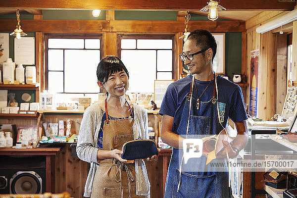 Lächelnde japanische Frau und Mann mit blauer Schürze und Brille stehen in einem Ledergeschäft.