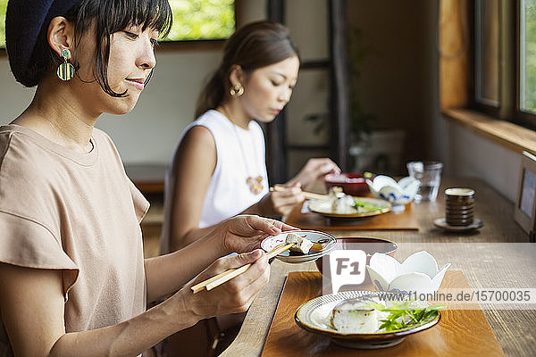 Two Japanese women sitting at a table in a Japanese restaurant  eating.