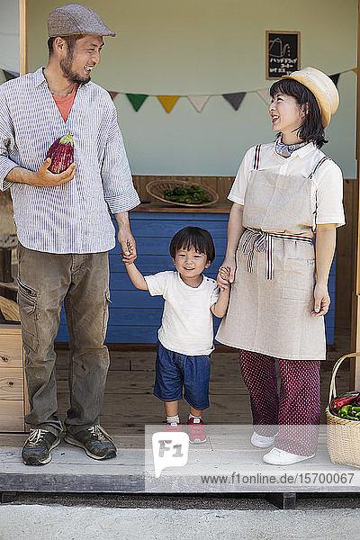Japanischer Mann  Frau und Junge stehen vor einem Bauernladen und halten Händchen.