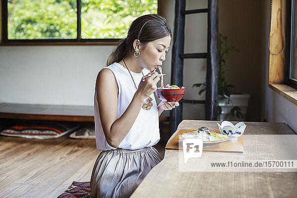 Japanese woman sitting at a table in a Japanese restaurant  eating.