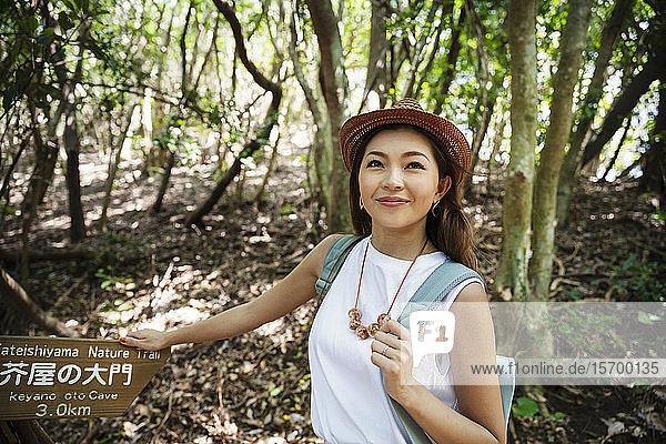 Japanische Frau mit Hut beim Wandern im Wald.