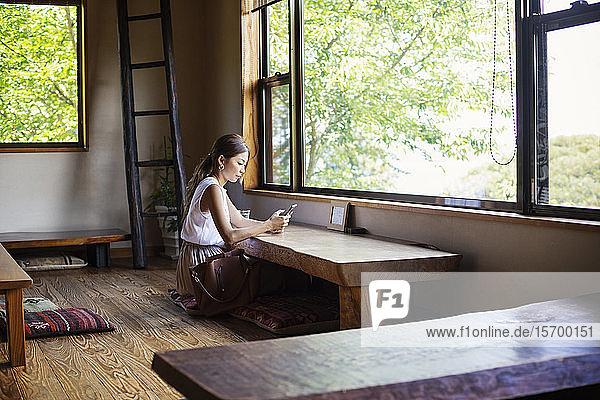 Japanerin  die an einem Tisch in einem japanischen Restaurant sitzt.