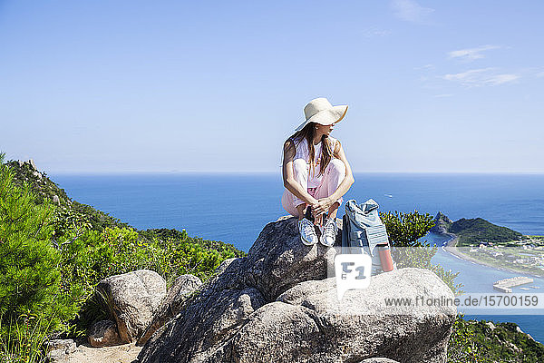 Japanese woman wearing hat sitting on rock on a cliff  ocean in the background.