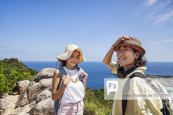 Zwei Japanerinnen mit Hüten stehen auf einer Klippe  im Hintergrund das Meer.