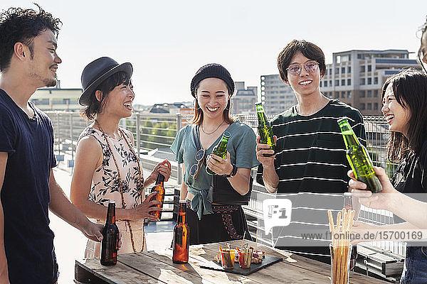 Gruppe junger japanischer Männer und Frauen  die auf einem Dach in einer städtischen Umgebung stehen und Bier trinken.