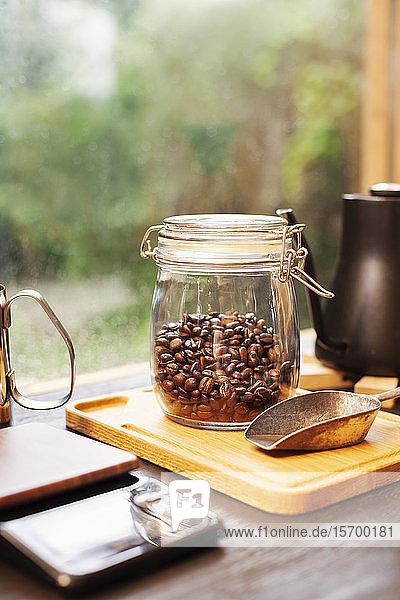 Nahaufnahme einer Kaffeekanne  eines Glasgefäßes mit Kaffeebohnen und einer metallenen Kaffeeschaufel auf einem Holzbrett. Nahaufnahme einer Kaffeekanne, eines Glasgefäßes mit Kaffeebohnen und einer metallenen Kaffeeschaufel auf einem Holzbrett.