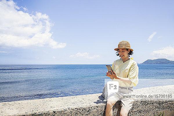 Japanische Frau mit Hut  die an einer Wand sitzt  im Hintergrund das Meer.