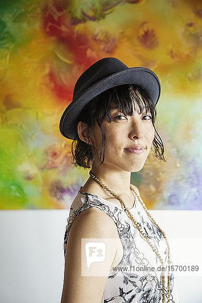 Japanische Frau mit Hut vor einem abstrakten Gemälde in einer Kunstgalerie.