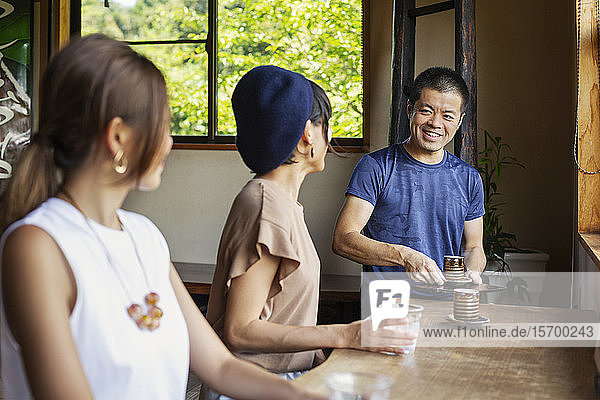 Waiter serving two Japanese women sitting at a table in a Japanese restaurant.
