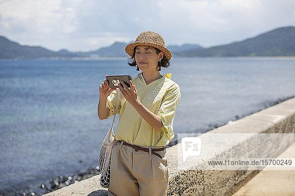 Japanische Frau mit Hut  die am Meer steht und mit dem Handy fotografiert.