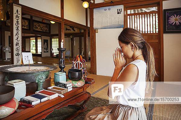 Two Japanese women kneeling in Buddhist temple  praying.