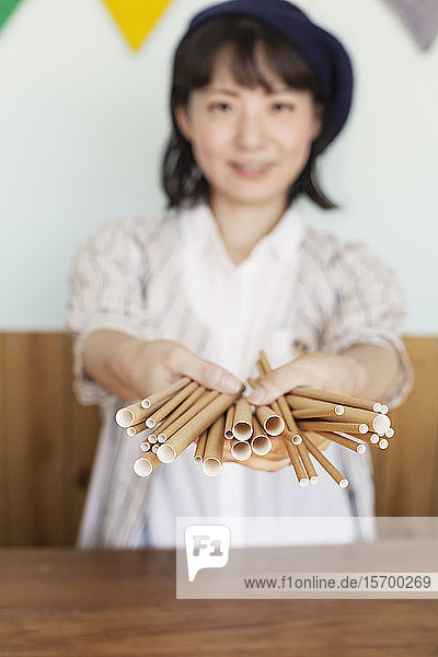 Japanese woman standing behind counter in a farm shop  holding bunch of cardboard rolls.