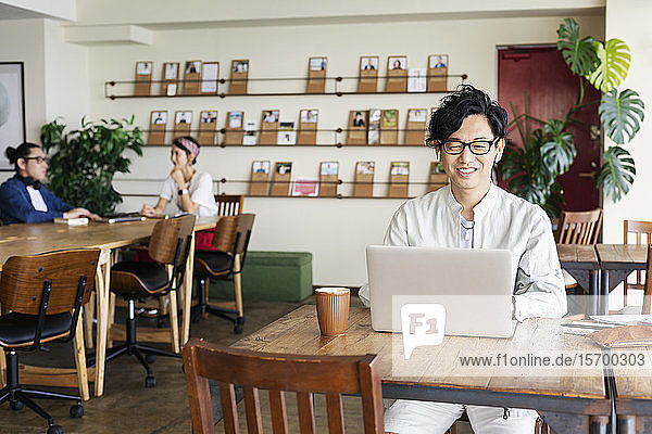 Group of young Japanese professionals working on laptop computers in a co-working space.