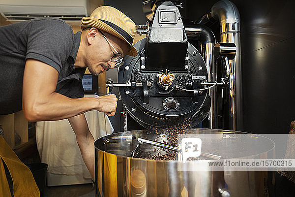 Japanese man wearing hat and glasses standing in an Eco Cafe  operating coffee roaster machine.
