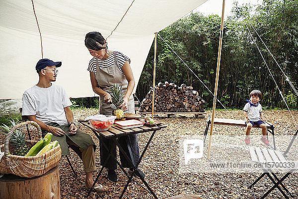 Japanischer Mann  Frau und Junge versammelten sich um einen Tisch unter einem Baldachin und bereiteten Gemüse zu.