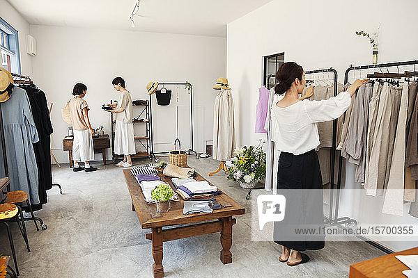 Drei Japanerinnen stehen in einer kleinen Modeboutique und betrachten Kleidung auf Schienen.