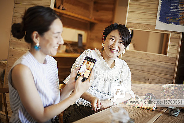 Two Japanese women sitting at a table in a vegetarian cafe  using mobile phone.