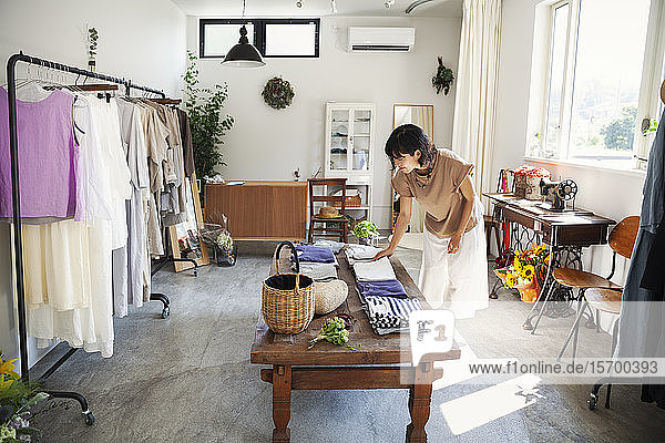 Japanese woman standing in a small fashion boutique  looking at T-Shirts on a coffee table.
