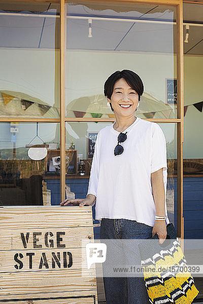 Japanische Frau steht vor einem Hofladen  hält eine Einkaufstasche in der Hand und lächelt in die Kamera.