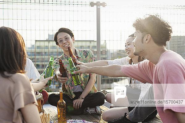 Gruppe junger japanischer Männer und Frauen  die auf einem Dach in einer städtischen Umgebung sitzen und Bier trinken.