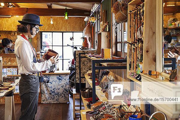 Japanische Frau mit Hut und Brille beim Stöbern in einem Ledergeschäft.