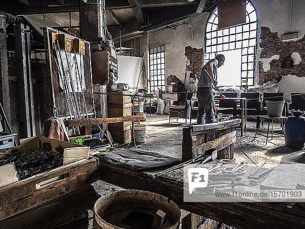 Italy  Veneto  Venice  Murano Island  Glassblowing art from Murano  a craftsman during the a craftsman working glass in a traditional glass factory