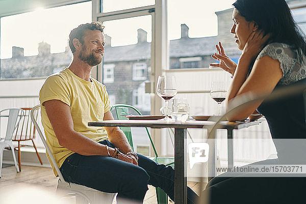 Ehepaar unterhält sich beim Essen im Restaurant