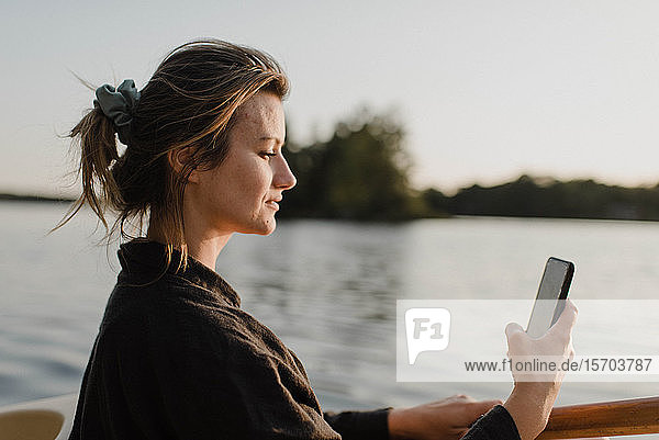 Frau mit Smartphone am See  Bobcaygeon  Ontario  Kanada