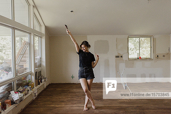 Frau hält Pinsel und tanzt in neuem Zuhause