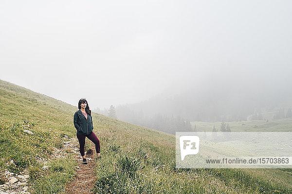 Frau wandert auf der Bergkuppe  dichter Nebel im Hintergrund